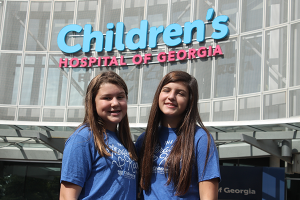 Two teenage girls smile in front of Children's Hospital of Georgia.